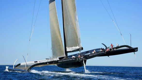 Обои Американский тримаран, изготовленный корпорацией BMW Oracle Racing, с экипажем на борту движется на большой скорости по морской водной поверхности на фоне безоблачного голубого неба