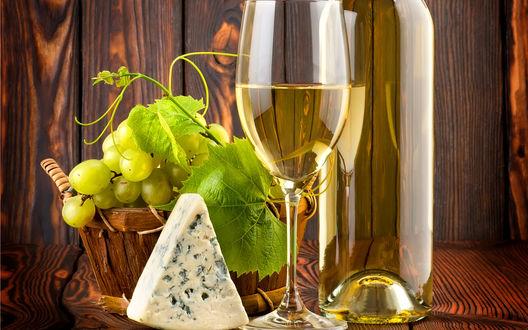 Обои На столе стоит бутылка белого вина с кусочком сыра и гроздью винограда