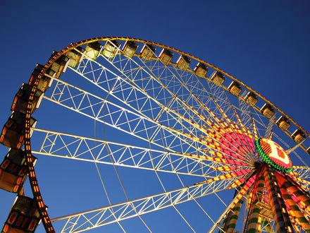 Обои Украшенное гирляндами колесо обозрения на фоне синего неба