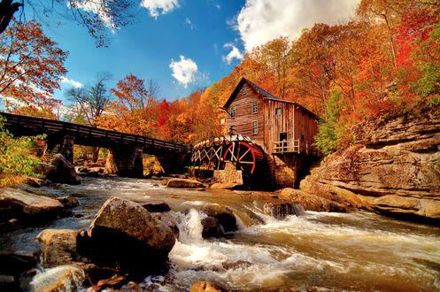 Обои Деревянная водяная мельница расположенная на быстрой горной речке со скалистыми берегами  и  пролегающим  через нее мостом на фоне деревьев, покрытых яркими желтыми и красными осенними листьями, и голубого неба с небольшими белыми облаками