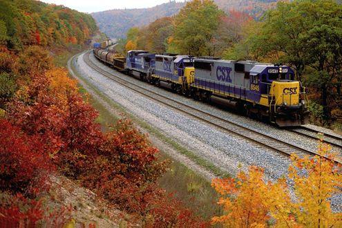 Обои Железнодорожный состав, состоящий из двух тепловозов и грузовых  вагонов различного назначения, двигается по рельсам, усыпанными серым гравием и проложенными в гористой местности на фоне деревьев,покрытых желтыми и красными осенними листьями