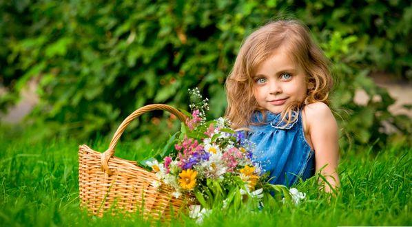 Обои Девочка с корзинкой цветов лежит на лужайке