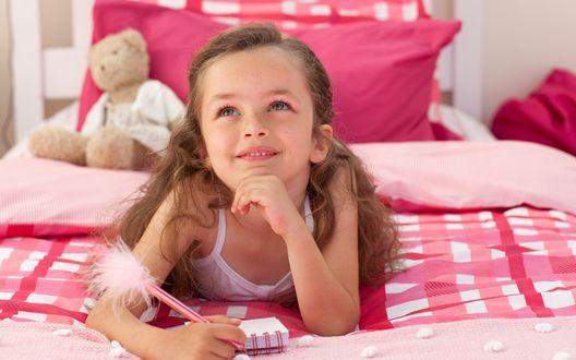 Обои Маленькая девочка с веснушками лежит на кровати и записывает свои мечты в маленький блокнотик
