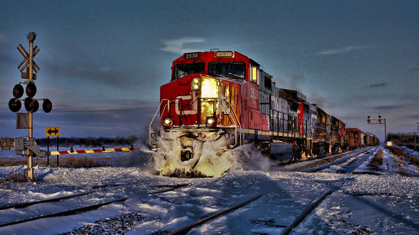 Обои Красно-синий тепловоз с прицепленными грузовыми вагонами движется по заснеженным рельсам в сумерках, проезжая мимо железнодорожного переезда с закрытым шлагбаумом