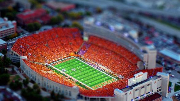 Обои Огромный стадион Nebraska с ярко-зеленым футбольным полем и оранжевыми трибунами для зрителей, расположенный в городе Линкольн, штат Небраска, Соединенные Штаты Америки, с эффектом тилт шифт / tilt shift