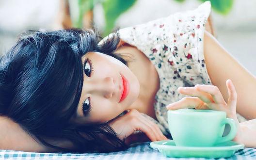 Обои Азиатская актриса и модель Ли Мин Чжон / Lee Min Jung положила голову на стол, рядом с бирюзовой чашкой на блюдце и нежно касается её пальцем