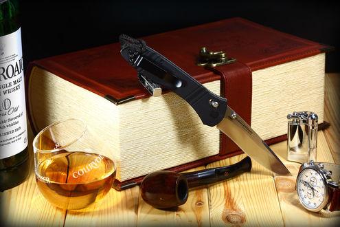 Обои На деревянном столе находятся: бутылка виски; бокал,наполненный виски; книга в кожаном переплете с застежкой; курительная трубка; зажигалка; наручные часы и складной нож марки McHenry&Williams / Мак Генри и Вилльямс произодство USA / США
