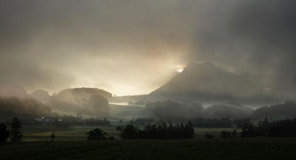 Обои Туманное утро среди долины позади которой виднеется гора или вулкан