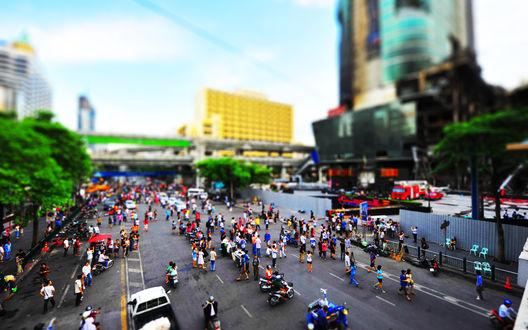 Обои Ratchaprasong Road в городе Bangkok, Thailand  / Бангкок, Таиланд с улицей, заполненной большим количеством людей и автотранспорта, на фоне небосребов и деревьев с зеленой листвой, с эффектом тилт шифт/ tilt shift