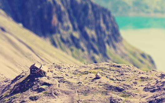 Обои У подножья высокой скалы на песчаной почве, расположены несколько небольших домиков, с эффектом тилт шифт / tilt shift