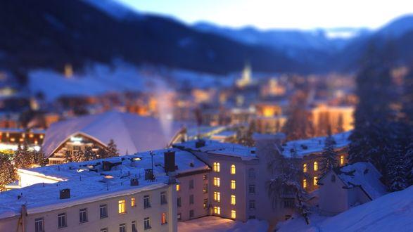 Обои Ночной вид города в горах с ярко освещенными многоэтажными домами, с заснеженными улицами и крышами домов, деревьями, с эффектом тилт шифт / tilt shift