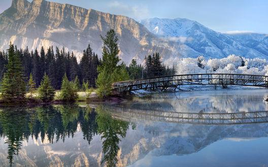 Обои Горная река с дугообразным металлическим мостом, соединяющим два противоположных берега, на одном деревья с зеленой листвой, на другом деревья, покрытые снегом на фоне гор и голубого неба