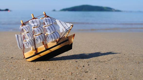 Обои Модель парусника на песке возле воды