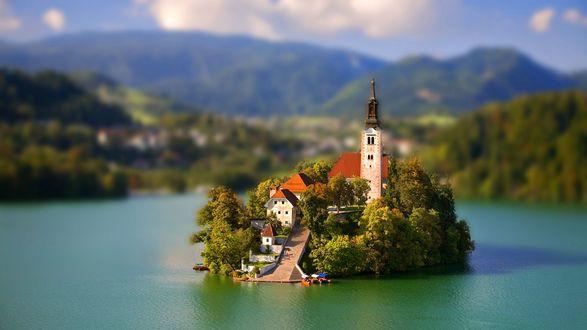 Обои Небольшой остров с несколькими домами и колокольней, к которым ведет широкая лестница, внизу у причала стоят лодки, с эффектом тилт шифт / tilt shift, Словения / Slovenia