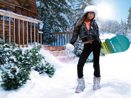 Обои Красивая чернокожая девушка со сноубордом в руках стоит возле заснеженного домика в окружении елей (Southpole Juniors)