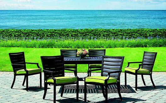 Обои Зеленая трава между террасой и морем, деревянный стол и шесть стульев, на столе стоит букет