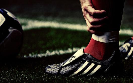 Обои Макро съемка: Нога игрока на футбольном поле, обутая в кроссовок фирмы Адидас / Adidas, рядом футбольный мяч