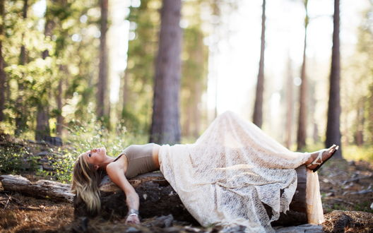 Обои Девушка в белой юбке и сером топе лежит на стволе дерева в лесу