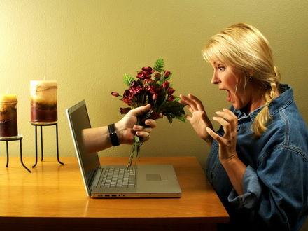 Обои На лице рыжеволосой девушки, сидящей за ноутбуком, восторг и удивление от неожиданно высунувшейся из монитора мужской руки с букетиком цветов