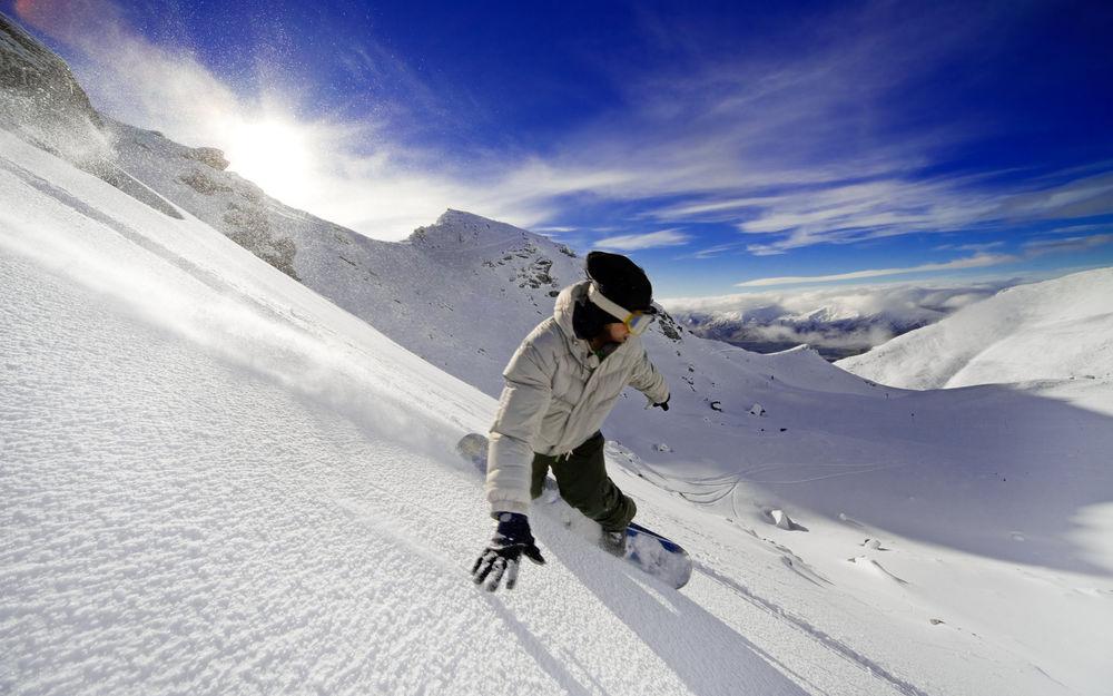 Обои для рабочего стола Парень катается на сноуборде в заснеженных горах