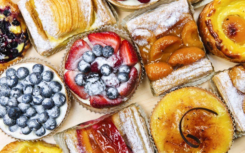 Обои для рабочего стола Разнообразные сладости с фруктами на столе, засахаренная клубника, черника на сдобе