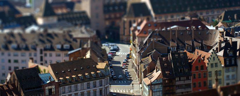 Обои Городские дома с пролегающей между ними небольшой улицей и с большим количеством припаркованных на ней легковых автомобилей, с эффектом тилт шифт / tilt shift