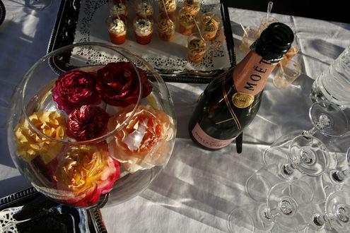 Обои Все готово к торжеству - открытая бутылка шампанского Moet, большая ваза с плавающими в ней цветами и маленькие порции дессерта рядом на столе