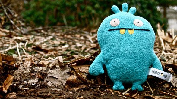 Обои Плюшевая голубая прикольная игрушка на фоне осенних листьев