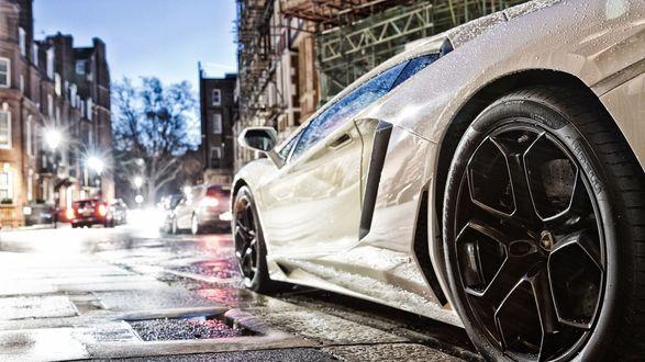 Обои Белый суперкар на улицах города, мокрый от капель дождя и сияющий, рвущийся на старт