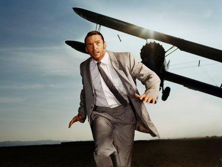 Обои Американский актер Хью Джекман / Hugh Jackman в деловом костюме с опаской смотрит вверх на пролетающий над ним на малой высоте самолет