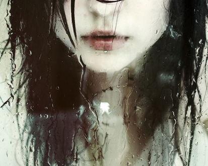 Обои Девушка стоит за  стеклом, покрытым каплями воды