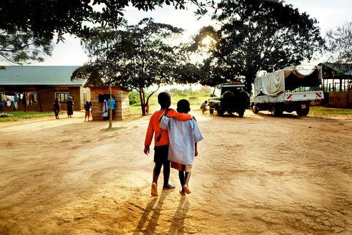 Обои Два чернокожих мальчика идут в обнимку по песку небольшой африканской деревни на фоне деревьев, автомобилей и яркого солнца