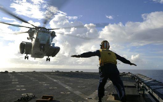 Обои Авиационный техник  руководит посадкой вертолета на авианосец, находящийся на океанских просторах
