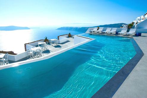 Обои Белые лежаки и вдоль бассейна и терасса отеля на фоне морской бухты среди гор