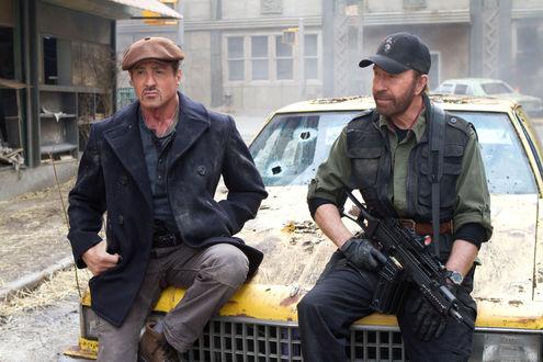 Обои Сильвестр Сталлоне / Sylvester Stallone и Чак Норрис / Chuck Norris у желтой разбитой машине в разрушенном городе из фильма Неудержимые 2 / The Expendables 2