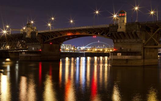 Обои Автомобильный мост, проложенный через реку, на поверхности которой отражаются разноцветными бликами осветительные дорожные фонари, на фоне ночного города
