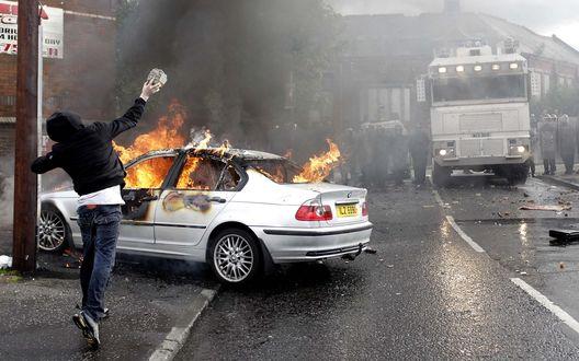 Обои Уличные беспорядки в городе, хулиган бросает камень в горящий легковой автомобиль, полицейские с помощью водометной машины готовятся решительно пресечь беспорядки