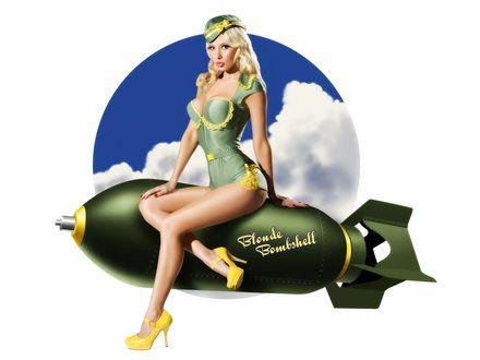 Обои Блондинка в камуфляжном купальнике и пилотке сидит на бомбе с надписью 'Блондинка Бомба' / Blonde Bombshell на фоне круга с голубым небом и белыми облаками