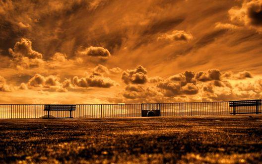Обои Скамейки стоят вдоль парапета на фоне золотистого неба