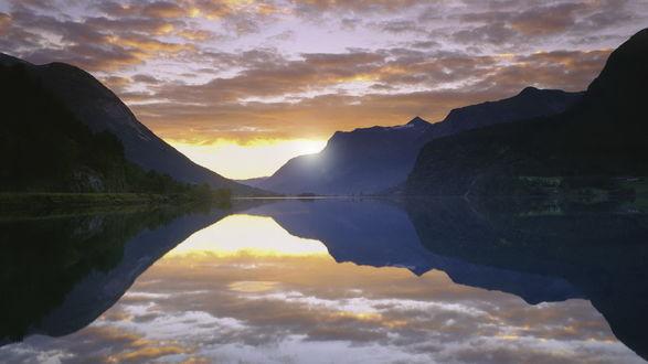 Обои Озеро в горах идеально отражает все, что расположено на его берегах, и лучи восходящего солнца, и горные вершины, и тучи, размеренно плывущие по небу