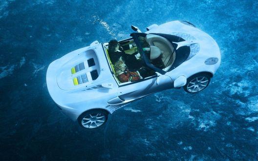 Обои Автомобиль, с сидящими в нем мужчиной и женщиной, погружается в морскую пучину