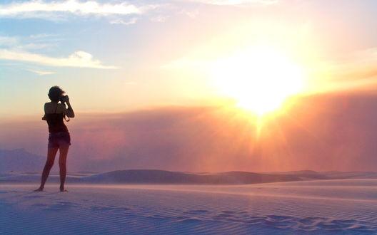 Обои Девушка, стоящая в песчаных барханах, навела свой фотоаппарат на яркое, восходящее солнце