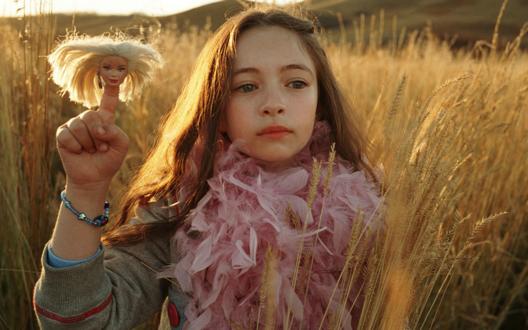 Обои Джелиза-роза из фильма 'Страна приливов'' / 'Tideland' держит в руках голову куклы барби по имени Мстик / Mistake и стоит посреди поля