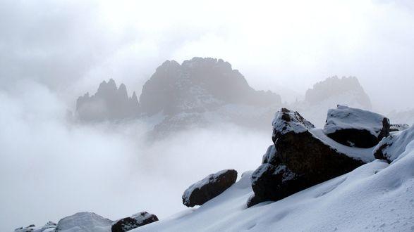 Обои Горные массивы засыпанные снегом с поднимающимся густым туманом