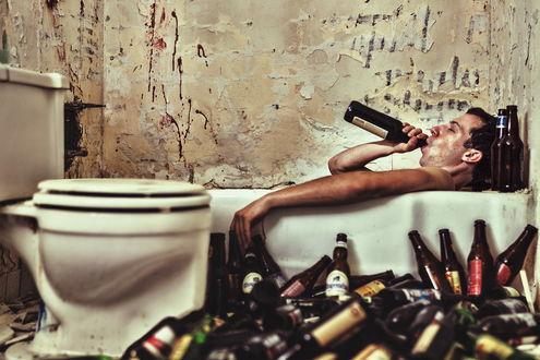Обои Мужчина лежит в ванной и пьет пиво, на полу лежит много пустых бутылок