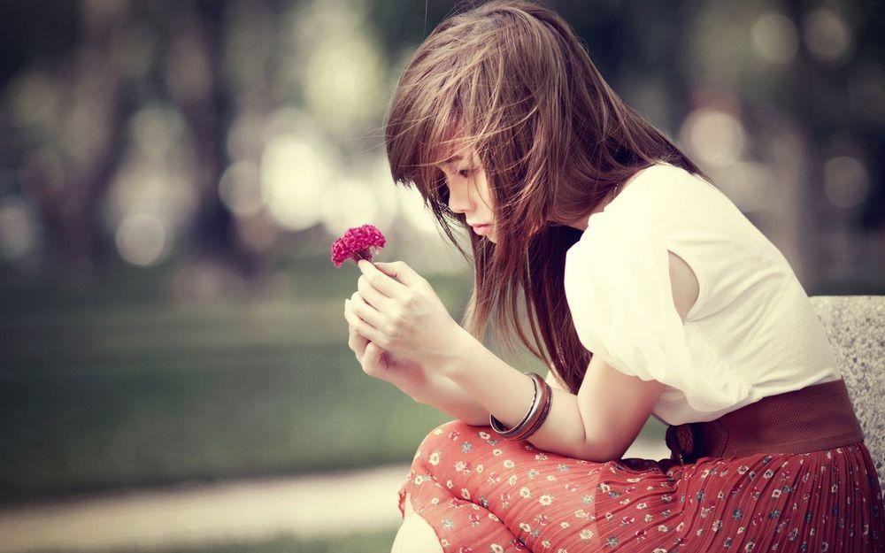 Обои для рабочего стола Грустная девушка сидит на бетонной лавочке и держит в руках красный цветок