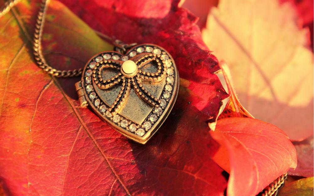 Обои для рабочего стола Красивый кулон со стразами в форме сердца лежит на желтых осенних листьях