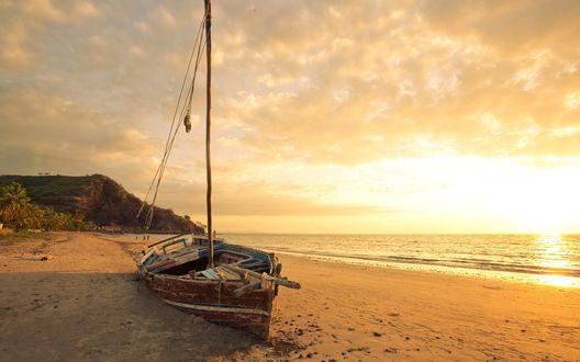 Обои Лодка, покренившись на бок, стоит на берегу моря