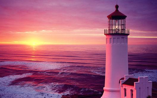Обои Маяк, стоящий на морском берегу, в лучах заходящего солнца