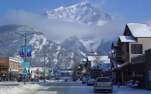 Обои Канада / Canada.Небольшой курортный городок, расположенный в предгорье высокой горы, заснеженные пики которой, поднимаются выше облаков